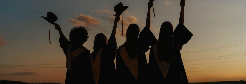 Graduates celebrating at sunset